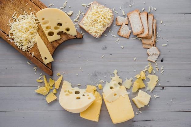 Fromage râpé avec des tranches et du pain sur un bureau en bois gris Photo gratuit