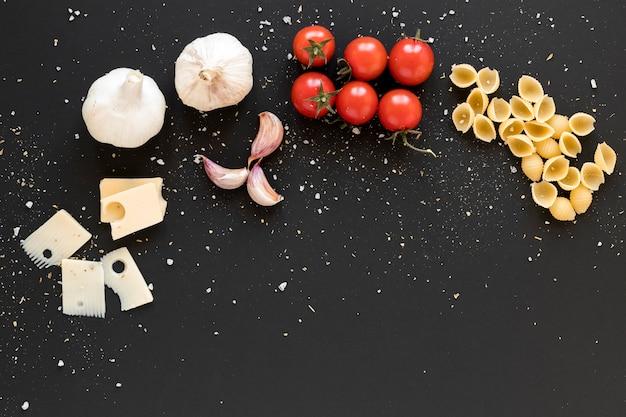 Fromage suisse; ail; tomates cerises et pâtes conchiglie sur fond noir Photo gratuit