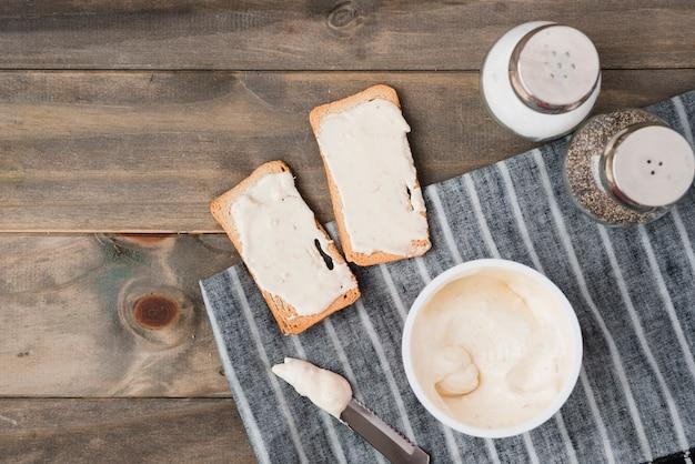 Fromage à tartiner sur le pain grillé avec salière et poivrière sur une table en bois Photo gratuit