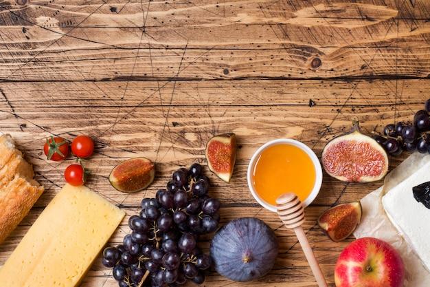Fromage, vin, baguette, figues, raisins, miel et collations sur le plateau de table en bois rustique avec espace de copie. Photo Premium