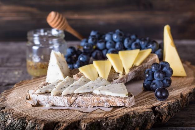 Fromages à la vigne, pain, miel. chèvre cheese.bruschetta nature morte de nourriture. petit déjeuner avec Photo Premium