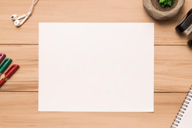 Frome ci-dessus d'une feuille de papier vierge entourée de fournitures de bureau Photo gratuit