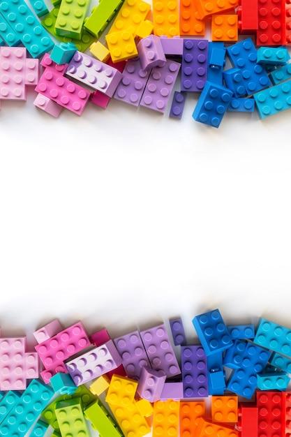 Frontière de briques de constructeur colorées plastick sur bois blanc. Photo Premium