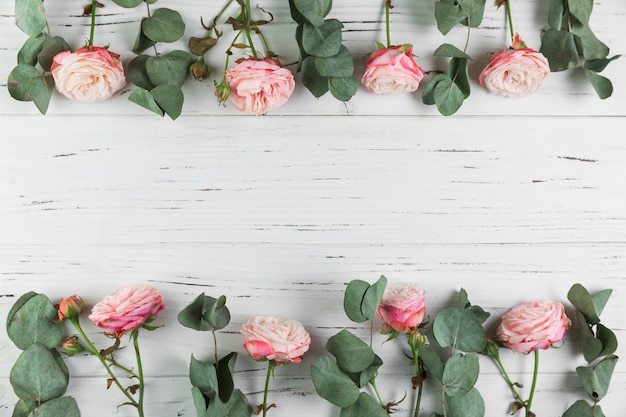 Frontière faite avec des roses roses et des feuilles sur un fond en bois blanc Photo gratuit
