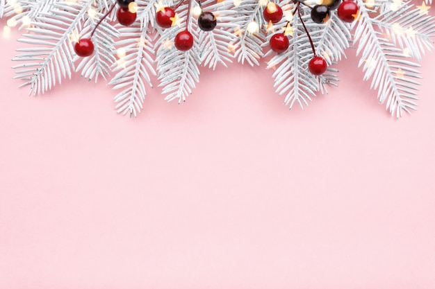 Frontière De Noël Avec Des Branches De Sapin, Rowan Et Lumières Dorées Sur Fond Rose Pastel, Espace Copie Photo Premium
