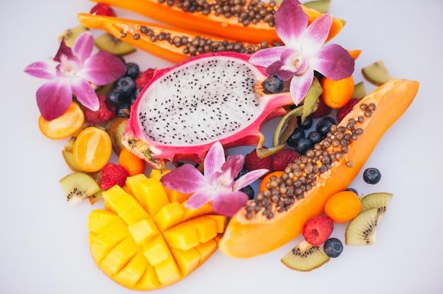 Fruit Dargon Mûr, Papaye, Kiwi, Mangue Au Kumquat, Orné De Belles Orchidées. Photo Premium