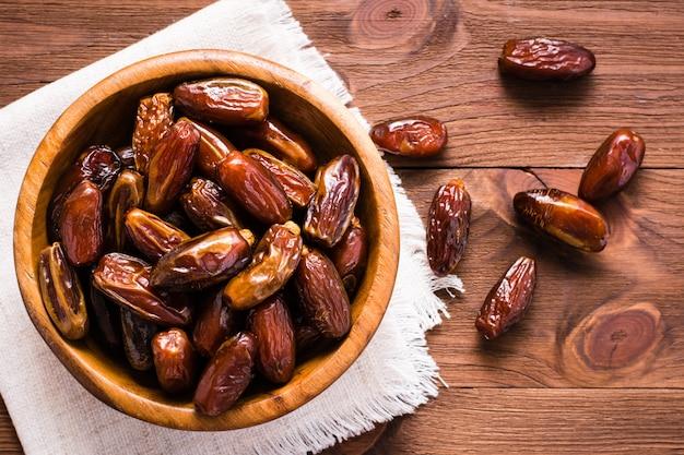 Fruit De Dattes Séchées Sucrées Dans Un Bol En Bois Et Sur La Table. Vue De Dessus Photo Premium