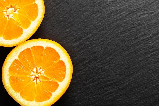 Fruit du concept alimentaire bio fruits orange ou pomelo coupés sur ardoise noire Photo Premium