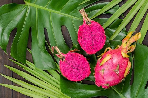 Fruit du dragon sur les feuilles de palmier et de monstre Photo Premium