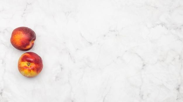 Fruit de pêche sur fond de marbre Photo gratuit