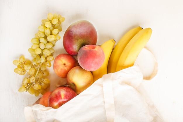 Fruits En Coton Blanc Réutilisable Sac Blanc Sur Fond De Bois Blanc Concept De Stockage Et De Recyclage Zéro Déchet Photo Premium