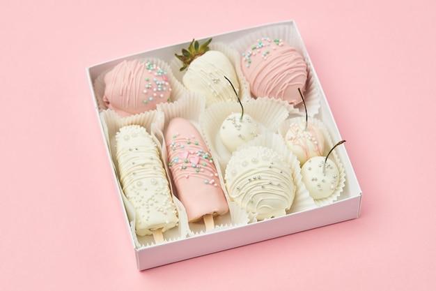 Les fruits enrobés de chocolat blanc et rose se trouvent dans une boîte cadeau Photo Premium