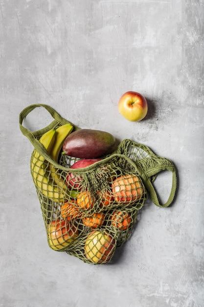 Fruits Frais Dans Un Sac De Ficelle Verte Sur Une Table Gris Clair. Bananes, Pommes, Oranges Et Mangues. Photo Premium