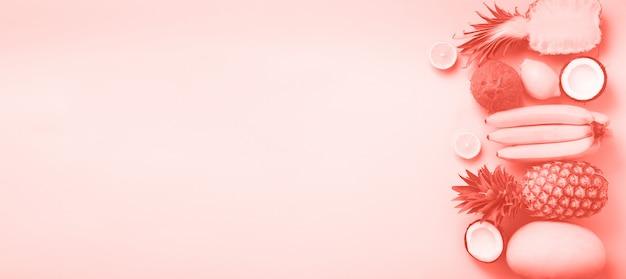 Fruits frais sur fond ensoleillé. concept monochrome avec banane, noix de coco, ananas, citron, melon de couleur corail. vue de dessus. espace de copie. pop art design, design créatif d'été. Photo Premium