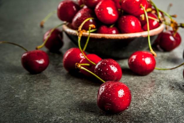 Fruits frais de saison frais et biologiques. cerise avec des gouttes d'eau sur une table en pierre sombre. fond Photo Premium