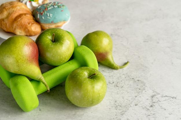 Fruits et haltère vert sur béton texturé Photo gratuit