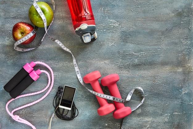 Fruits, haltères, une bouteille d'eau, corde, mètre, joueur sur bleu Photo Premium