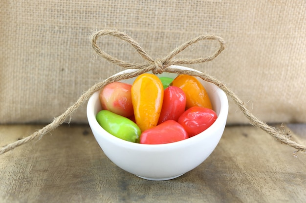 Fruits De L'imitation Supprimable (kanom Look Choup) Dans Un Petit Bol Blanc Sur Une Table En Bois Et Un Fond De Sac. Photo Premium