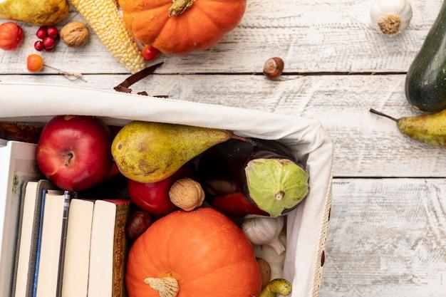 Fruits et légumes sur un panier avec des livres Photo gratuit