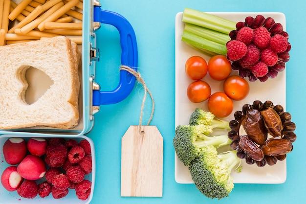 Fruits et légumes près de la jolie boîte à lunch Photo gratuit