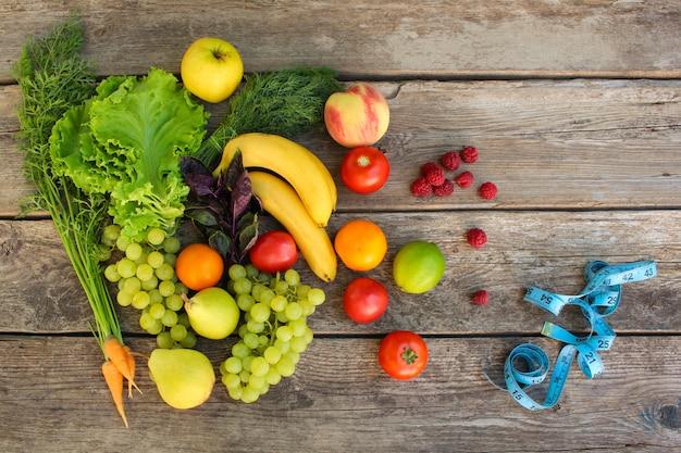 Fruits, légumes, ruban à mesurer sur fond en bois. Photo Premium