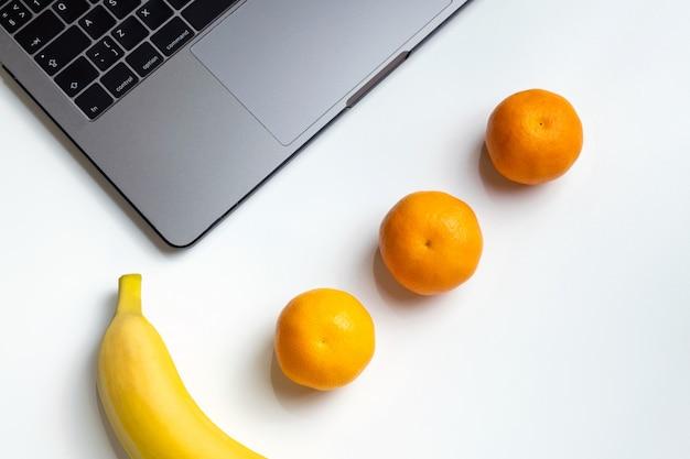 Fruits sur le lieu de travail. ordinateur portable, banane, mandarines et jus d'orange sur un bureau blanc. Photo Premium