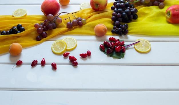 Fruits mélangés sur une écharpe jaune sur une table blanche, vue de coin. Photo gratuit