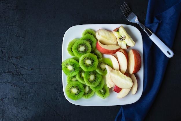 Fruits mélangés kiwi frais et pommes avec des raisins dans une assiette sur une table en bois. Photo Premium