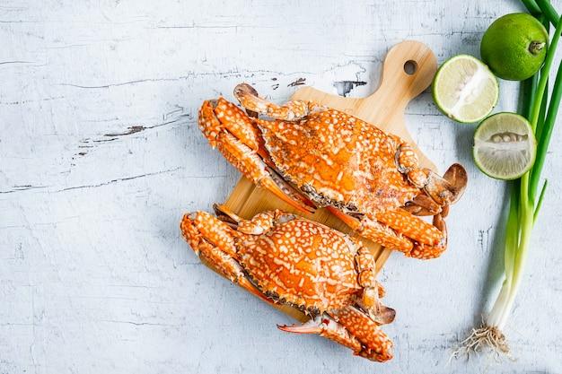 Fruits de mer cuits à la vapeur de crabe sur un fond de bois blanc Photo Premium