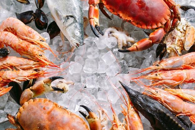 Fruits de mer sur glace. crabes, esturgeons, crustacés, crevettes, rapana, dorado, sur glace blanche. Photo Premium