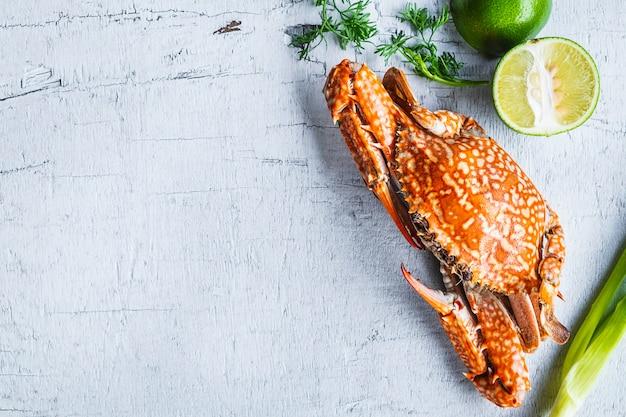 Fruits de mer à la vapeur de crabe sur bois blanc Photo Premium
