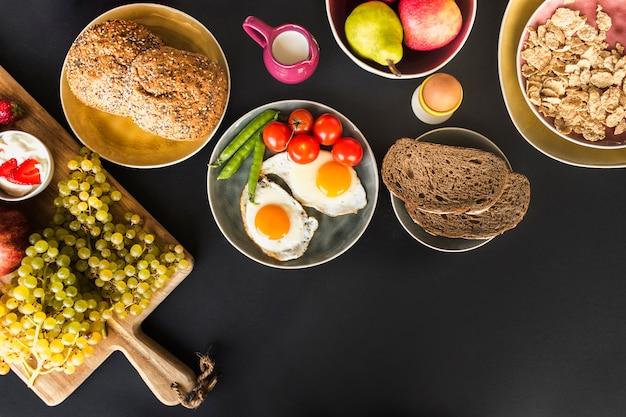 Fruits, muesli, fruits et omelette frite avec tomates et petits pois sur fond noir Photo gratuit