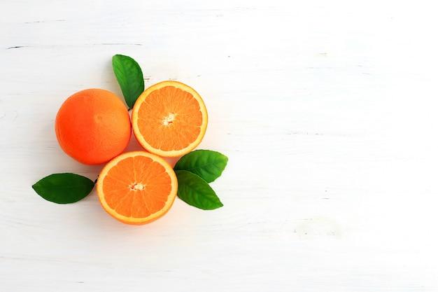 Fruits orange et un coupé en deux, avec des feuilles isolées sur fond blanc. Photo Premium
