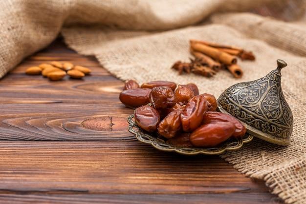 Fruits séchés dates sur plaque avec cannelle et noix Photo gratuit