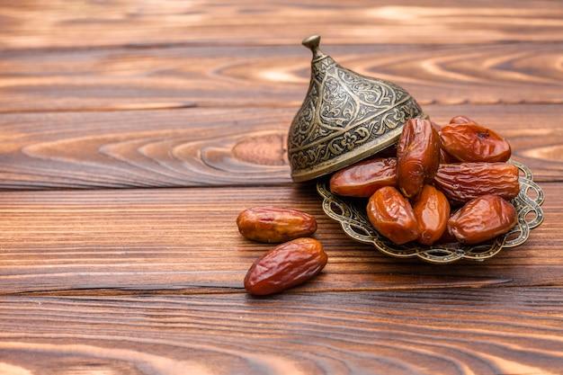 Fruits secs dates sur plaque sur une table en bois Photo gratuit
