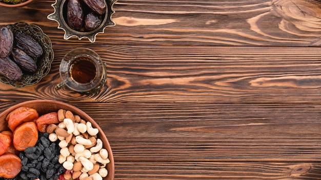 Fruits secs mélangés; des noisettes; dates et thé au festival de ramadan sur le bureau en bois Photo gratuit