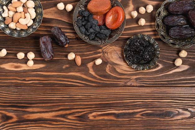 Fruits secs; noix et dates fraîches sur la table de texture en bois Photo gratuit