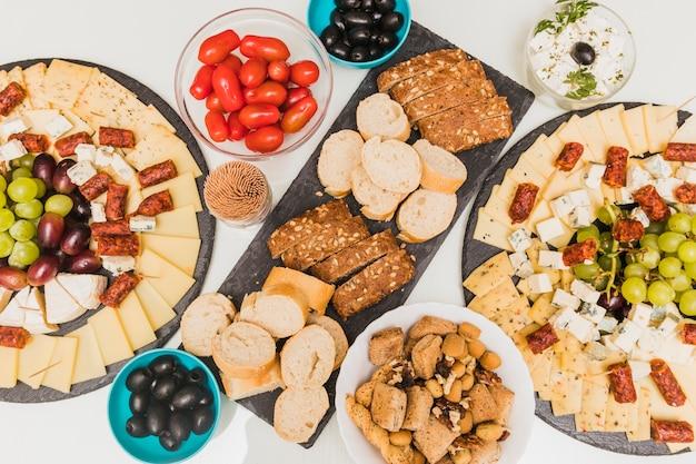 Fruits secs, olives, tomates et plateau de fromages avec raisins et saucisses fumées Photo gratuit