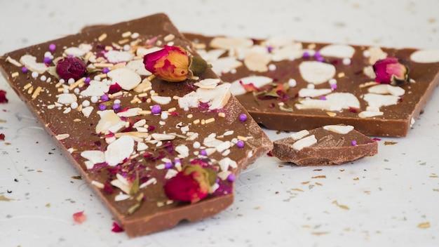 Fruits secs et pétales de rose sur une barre de chocolat mangée Photo gratuit