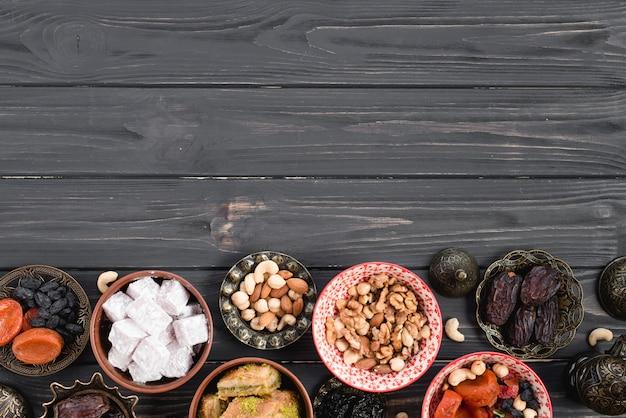 Fruits secs turcs frais; des noisettes; bonbons pour le ramadan sur un bureau en bois noir Photo gratuit