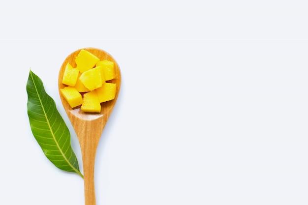 Fruits tropicaux, tranches de cube de mangue et feuille avec une cuillère en bois sur fond blanc. Photo Premium