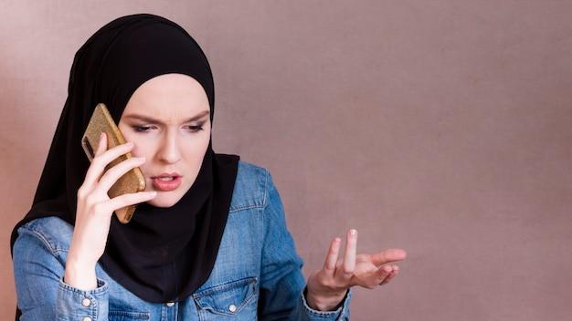 Frustré; femme arabe parlant sur smartphone, faisant le geste de la main Photo gratuit