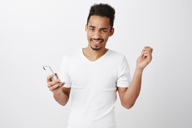 Frustré Et Mécontent De L'écouteur De Décollage De Gars Afro-américain Et Grincer Des Dents, Tenant Un Téléphone Mobile Photo gratuit