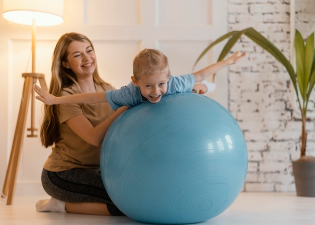 Full Shot Woman Holding Kid Sur Ballon De Gym Photo gratuit