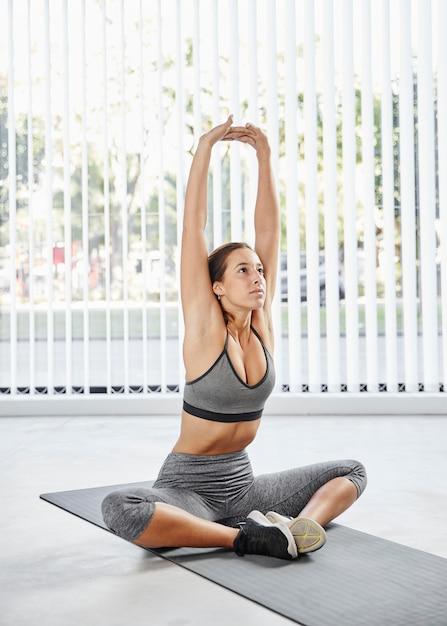 Full Shot Woman Stretching Sur Tapis De Yoga Photo gratuit