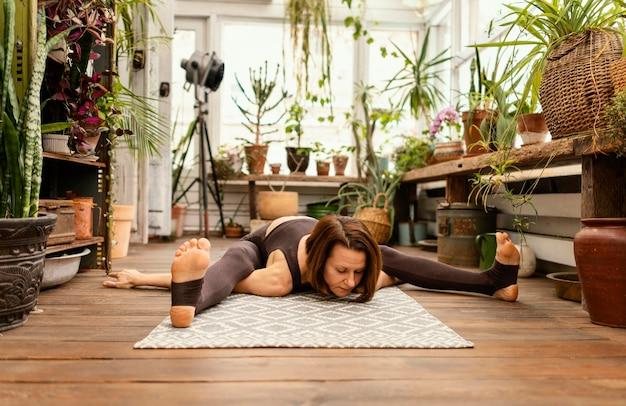 Full Shot Woman Stretching Sur Tapis Photo gratuit