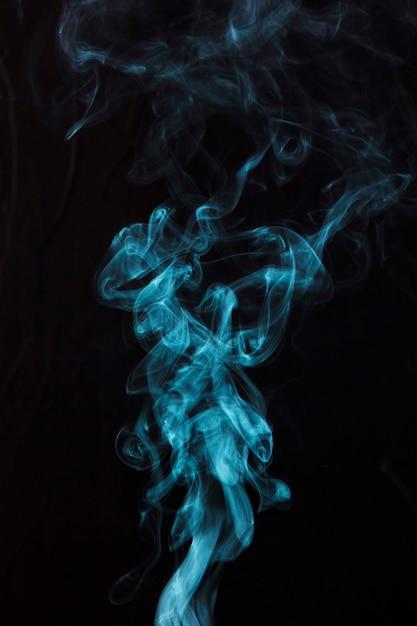Fumée bleue sur fond noir avec espace de copie pour l'écriture du texte Photo gratuit