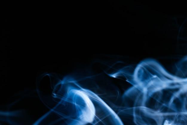 Fumée bleue ondulée sur fond noir Photo gratuit