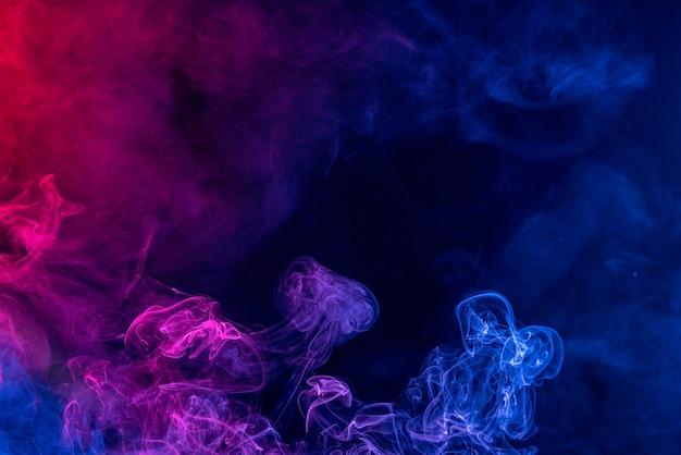 Fumée De Couleur Rouge Et Bleue Colorée Isolée Sur Fond Noir Photo Premium
