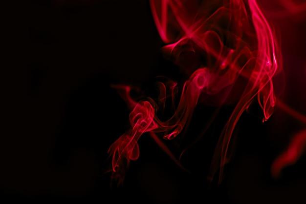 Fumée rouge sur fond noir Photo Premium